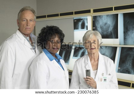 Portrait of three doctors posing for the camera - stock photo