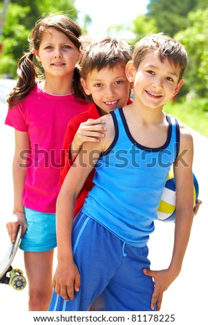 Portrait of three embracing children looking at camera and smiling - stock photo
