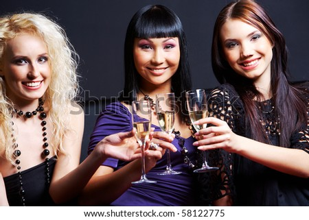 Portrait of three fashionable young women with flutes looking at camera - stock photo