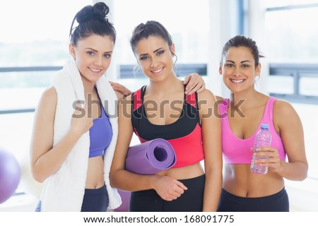 Portrait of three fit young women smiling in a bright exercise room - stock photo