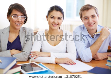 Portrait of three friendly students looking at camera - stock photo