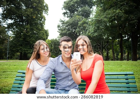 Portrait of three friends having fun with a mobile phone - stock photo