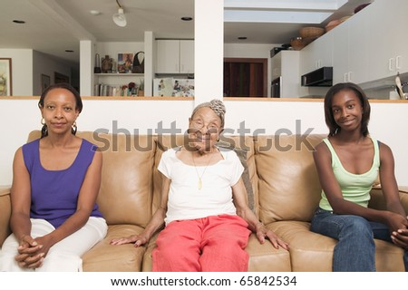 Portrait of three generations of women sitting on couch - stock photo
