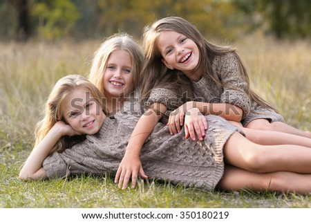 Portrait of three girl friends on the nature - stock photo