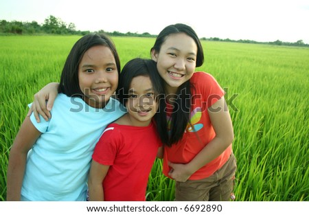 Portrait of three girls in the rice field. - stock photo