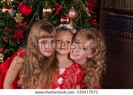 Portrait of three girls sitting on the carpet at the Christmas tree. The girls in beautiful red dress posing in Christmas decorations