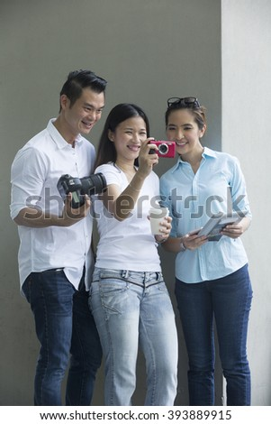 Portrait of three happy Asian friends taking photos with there camera's. A group of Chinese friends having fun shooting photos.