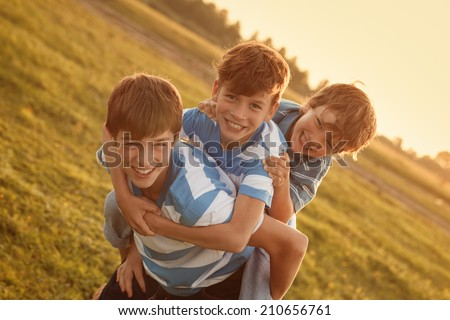 Portrait of three happy cheerful brothers at sunset, outdoor - stock photo