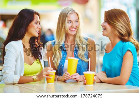 Portrait of three happy girls having drink while discussing their shopping - stock photo
