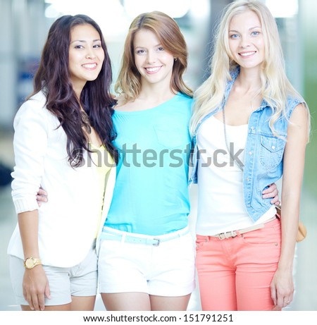 Portrait of three happy girls in smart casual looking at camera