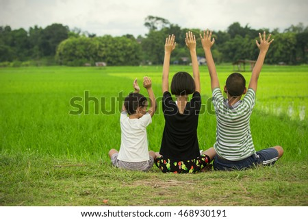 Portrait of three happy kids, boy and girls sitting in the grass to lift up the hands for yoga training.