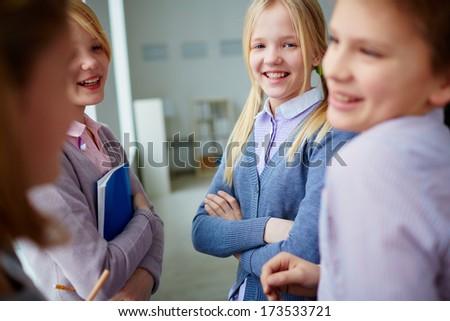 Portrait of three happy schoolgirls and schoolboy talking during school break - stock photo