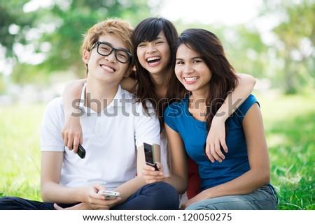 Portrait of three happy teenage friends sitting on grass - stock photo