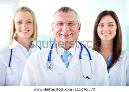 Portrait of three happy therapeutists looking at camera - stock photo