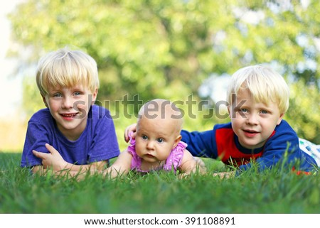 Portrait of Three happy young siblings: a young child, his little brother and their baby girl sister are laying outside in the grass on a summer day. - stock photo