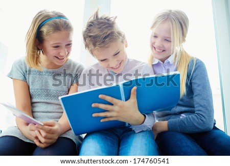 Portrait of three laughing classmates looking at notes in exercise book of schoolboy while he writing - stock photo