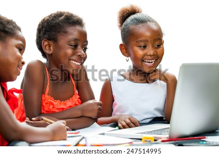 Portrait of three little African girls laughing at scene on laptop at desk.Isolated on white background.  - stock photo