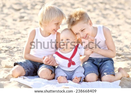 portrait of three little boys on the beach in summer