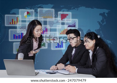 Portrait of three multi ethnic business people discussing business plan in office with business chart background - stock photo