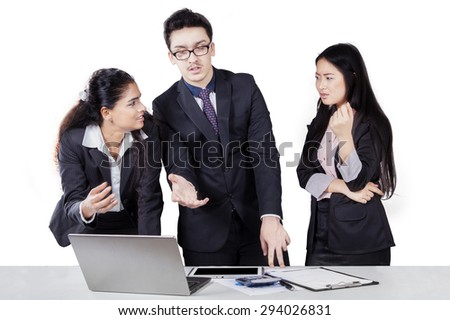 Portrait of three multi ethnic businesspeople in discussion and debating with laptop, isolated on white - stock photo