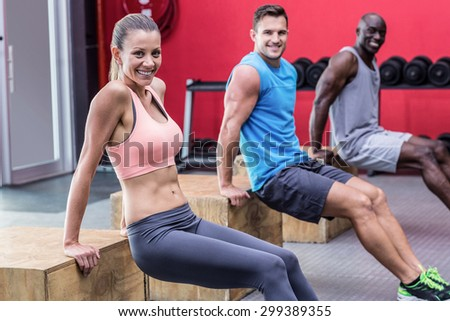 Portrait of three muscular athletes doing reverse push up - stock photo