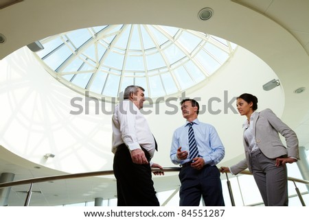 Portrait of three partners discussing ideas at meeting - stock photo