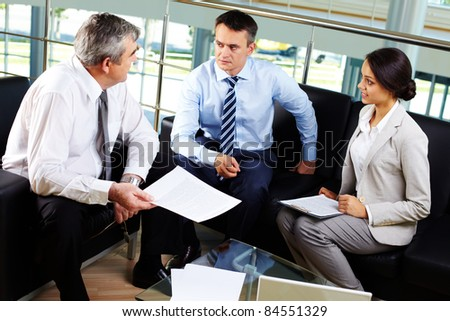 Portrait of three partners discussing new working plan at meeting - stock photo