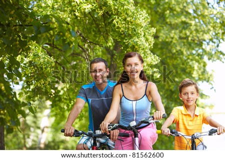 Portrait of three people cycling in wood - stock photo