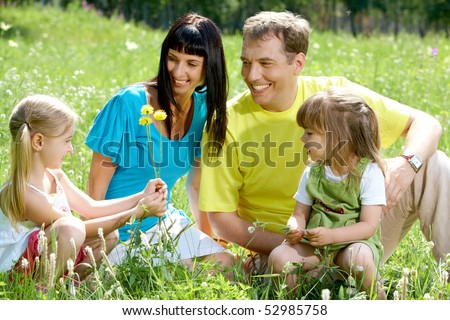 Portrait of three people looking at little girl while spending time outdoors - stock photo