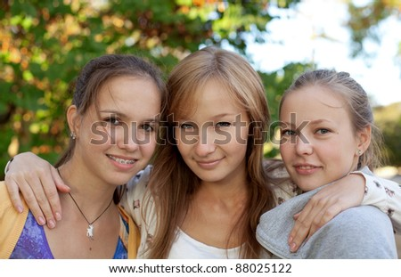 Portrait of three pretty student girls in the park - stock photo