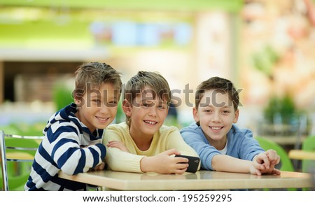 Portrait of three schoolboys sitting at table and looking at camera - stock photo