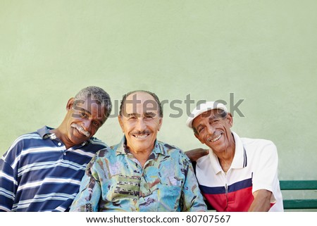portrait of three senior men looking at camera against green wall and smiling. Horizontal shape, copy space - stock photo