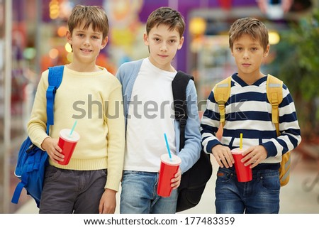 Portrait of three serious schoolboys with soda - stock photo