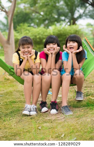 Portrait of three sisters sitting in hammock - stock photo