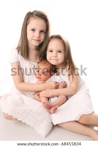 Portrait of three sisters, two little girls with a newborn all dressed in white dresses - stock photo