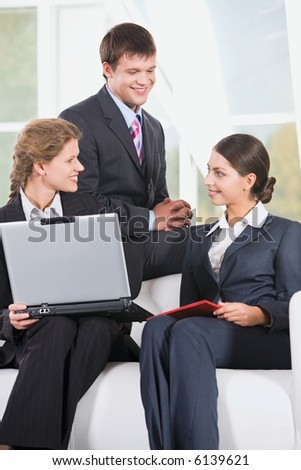 Portrait of three smiling business people sitting on the sofa and discussing a working questions