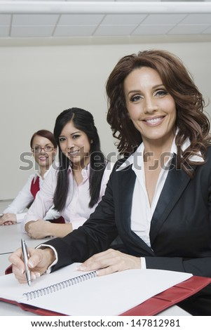 Portrait of three smiling multiethnic businesswomen sitting at office desk - stock photo