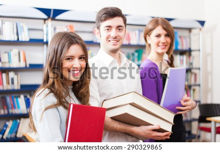 Portrait of three smiling students in a library - stock photo