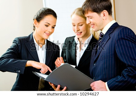 Portrait of three smiling young specialists looking at business plan with one of businesswomen pointing at something in it