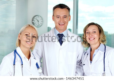 Portrait of three successful clinicians looking at camera with smiles - stock photo