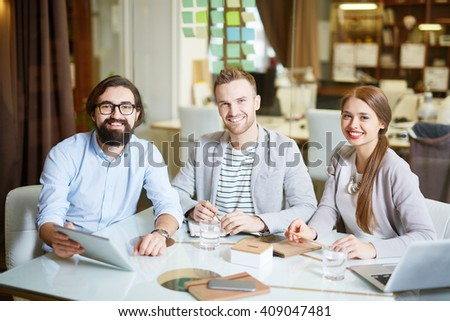 Portrait of three successful colleagues sitting at table and smiling - stock photo