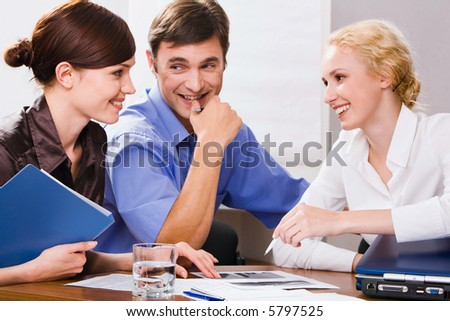 Portrait of three successful professionals smiling in a working environment