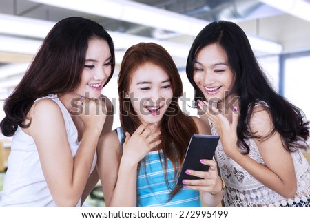 Portrait of three teenage girls standing in the classroom while reading a message and laugh together - stock photo