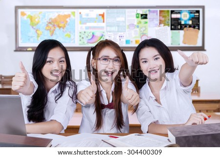 Portrait of three teenage students back to school and showing thumbs up in the classroom - stock photo