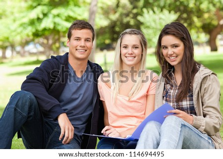Portrait of three teenagers studying together in a park - stock photo