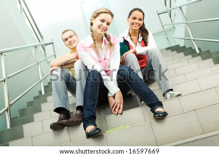 Portrait of three teens sitting on stairs and looking at camera in the  college - stock photo