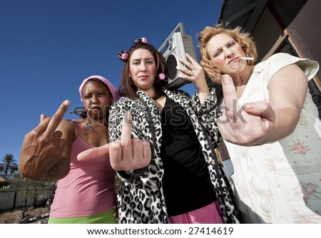 Portrait of three trashy women outdoors making a rude hand gesture - stock photo