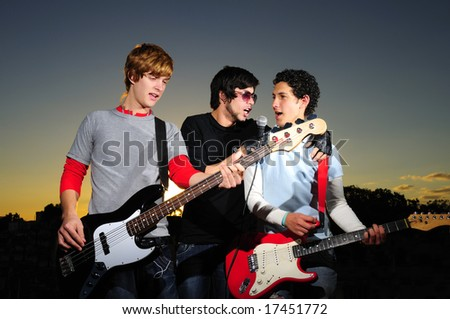 Portrait of three trendy teenagers playing music outdoors