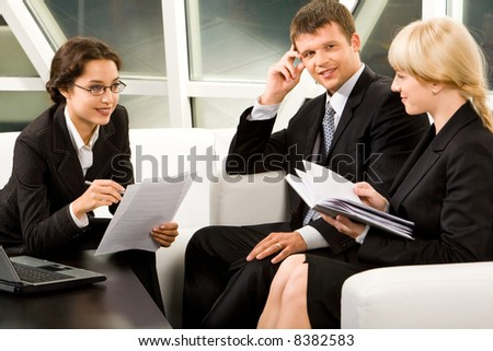 Portrait of three white collar workers discussing a new idea