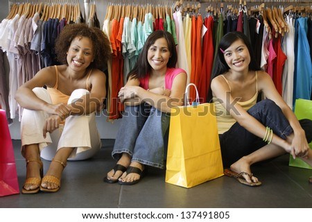 Portrait of three women sitting in clothing store - stock photo